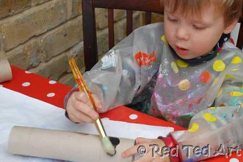 preschooler painting toilet paper rolls for dog puppet