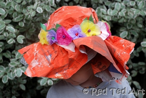 Preschooler wearing newspaper hat with spring flowers