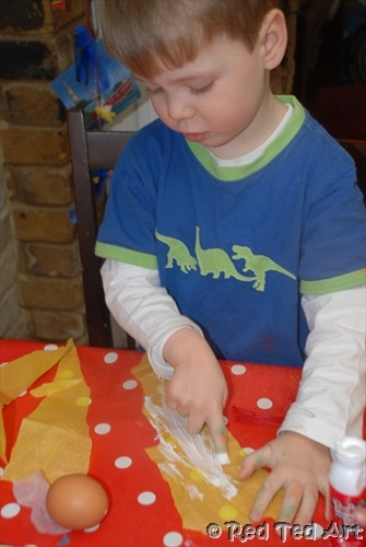 Preschooler adding glue to tissue paper to cover an egg shell