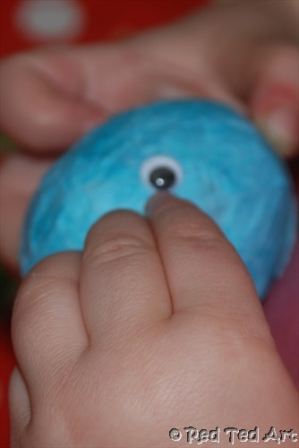 Preschooler adding googly eyes to tissue paper egg