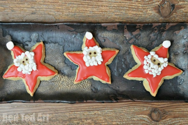 Easy Santa Star Cookies - super cute and quirky Santa Stars. The kids will adore helping to make these, and enjoy eating them even more. They would make great Edible Ornaments and perfect for Christmas School Bake Sales. Check out our easy recipe today!