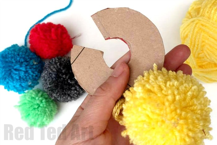 How to make a yarn pom pom with cardboard discs - the traditional way of pom pom making with kids. Reusable pom pom making DIY. #pompoms #pompom #howtomakeapompom #cardboard