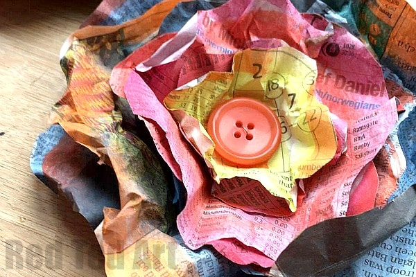 How to make a Newspaper Flower - Newspaper Flowers DIY - such a super pretty chabby chic flower DIY. These are quick to make - are nice and big (or small if you prefer) and a great way to decorate quickly and inexpensively. We do love upcycled Newspaper DIYs and these watercolor newspaper flowers are just gorgeous. Love those buttons in the centre!