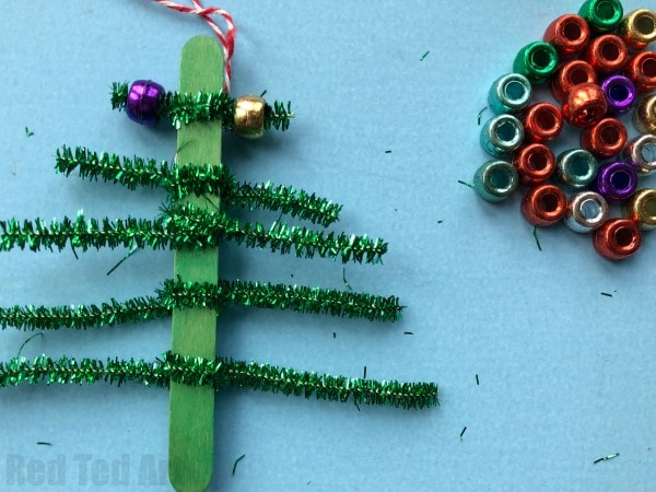 Pipecleaner Christmas Tree Ornaments - super cute and simple craft stick and pipecleaner tree ornaments. The kids will love to make these and they are great for fine motor skills. We made these at the school fair and they went down a treat! #Christmas #Christmastree #preschool #pipecleaner #ornaments