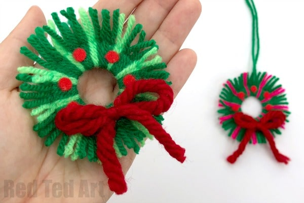 Add details to your yarn wreath ornament, such as bows or felt baubles