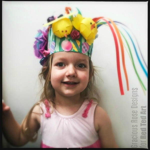 Preschooler wearing cheerful Easter Hat made from paper, with chicks and rainbow