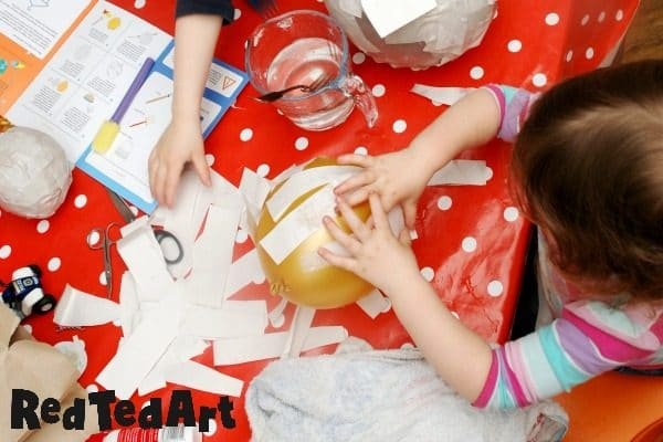 toddler making balloon paper mache