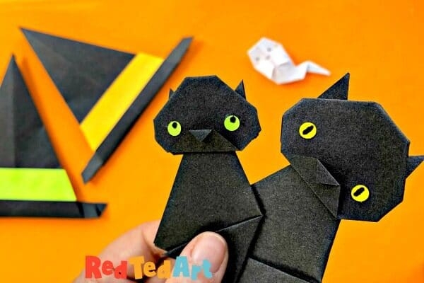 3 little black cats made from origami paper with paper witch hat and origami ghost