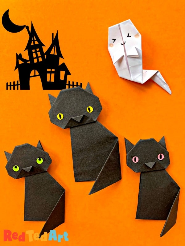 3 little black cats made from origami paper with Halloween background and ghost