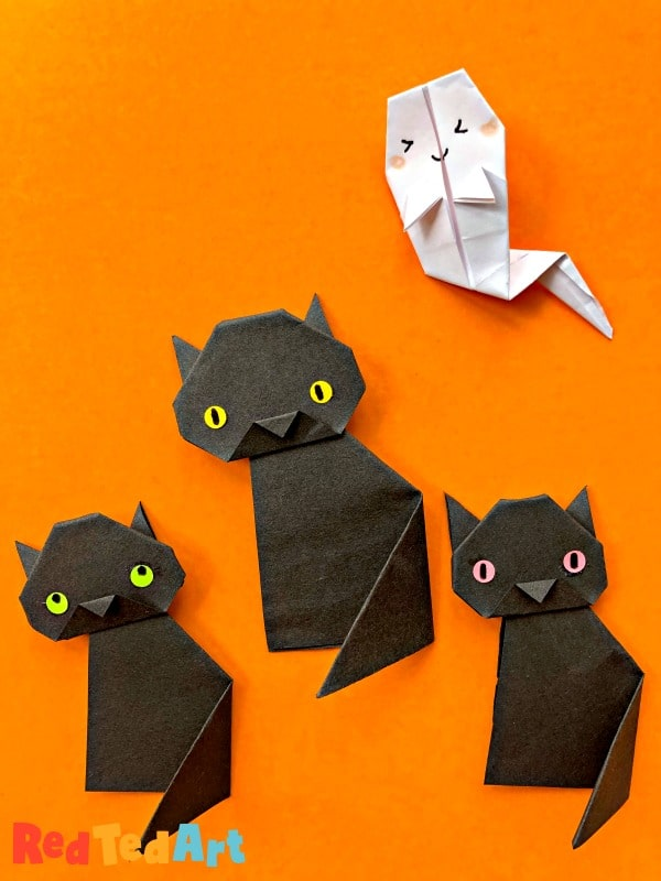 3 little black cats made from origami paper with paper ghost