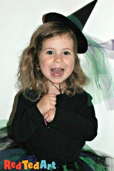 Toddler wearing an easy to make paper witch hat as part of her Halloween costume