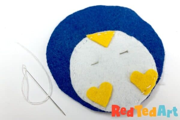 Pin the tummy to the Felt Penguin and sew with a running stitch